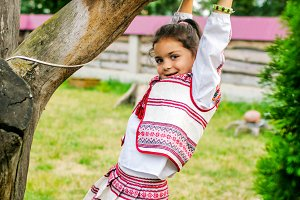 A beautiful girl playing on a tree