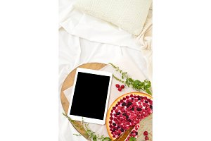 Flat lay breakfast in bed with raspberry cheesecake, mint tea and open note book, tablet