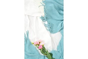 Flat lay pink flowers on white blanket with turquoise plaid