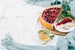 Toned top view of breakfast in bed with raspberry cheesecake, mint tea and paid