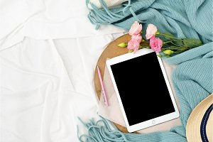 Flat lay tablet and flowers on white blanket with turquoise plaid