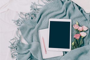 Toned Flat lay tablet and flowers on white blanket with turquoise plaid