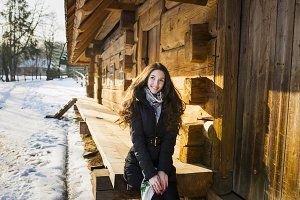 Cute girl sits at a wooden house