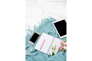 Vertical Flat lay tablet, phone, cup of coffee and flowers on white blanket with turquoise plaid