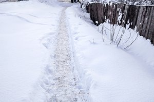 The path in the winter in the open air in the park. Snow-covered road in city, traces of boots in the snow. With wooden old fence of boards.