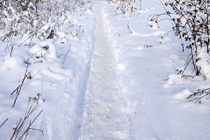 The path in the winter in the open air in the park. Snow-covered road in the city, traces of boots in the snow.