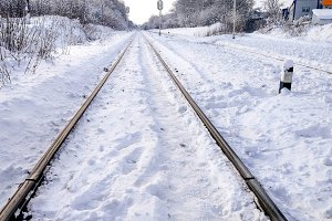 The path between the sleepers in with a bliss. Sleepers from the train, electric train in city in the winter. They are covered with snow from a storm. The road going into the distance.