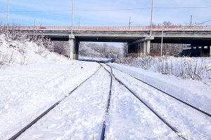 An automobile bridge across the railway crossing. Sleepers from the train, electric train in the city in the winter. They are covered with snow from a storm. The road going into the distance.