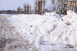 Snow cleaning in winter in city. Large piles of snow collected by cars on roadside. Cleared asphalt for cars.