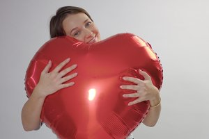 caucasian woman hugs a huge red heart and hold it
