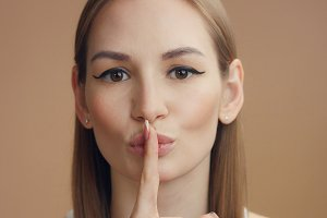 woman's portrait makes shhhh with a finger