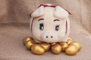 Pig doll on golden easter egg