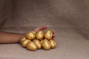 Human hand with heap of golden egg
