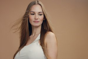 beauty woman model in studio on beige background with wind in hair bllowing it