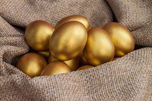 Heap of golden easter egg on brown