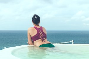 Woman relaxing in infinity swimming pool looking at view. Bali island.