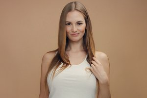 beauty woman model in studio on beige background touches her straight blonde hair