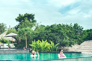 BALI, INDONESIA - JANUARY 10, 2018: Couple taking shoots in the swimming pool.