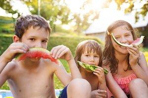 Children eating watermelon in the garden