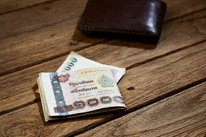 brown leather wallet and Thai money