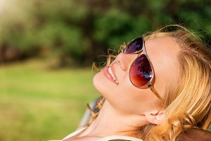Young woman wearing sunglasses in sunny summer nature