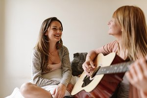 Beautiful friends playing guitar.