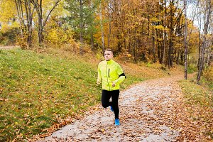 Young athlete with smartphone running in park in autumn.