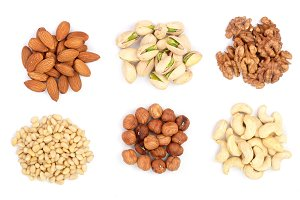 mixed of nuts heap isolated on white background. Almonds, cashews, hazelnuts, pine nuts and walnuts. Top view. Flat lay