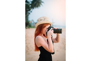 young woman photographer doing photo on the beach, close-up