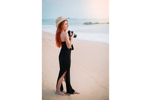 young woman photographer stands on the beach with a camera in hands