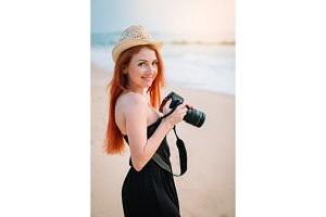 young woman photographer stands on the beach with a camera in hands, close-up