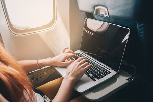 woman uses a laptop while on a plane