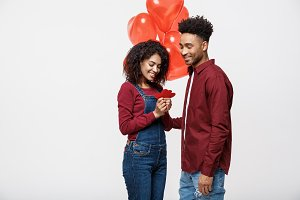 Portrait of young couple in love holding red paper heart and balloon.