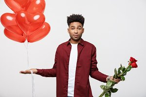 Valentine's Day: African American man holding red rose and balloon with disappointed expression.