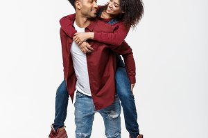 Full length young attractive african american lady riding back on her boyfriend back and enjoy playing to each other.