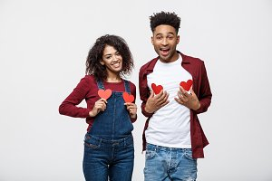 Portrait of african american cheerful couple holding red paper heart enjoy playing standing over grey background