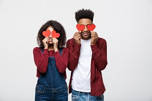 Beautiful Afro African American couple is holding red paper hearts and smiling, on gray background