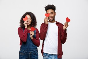 Beautiful Afro American couple holding two red paper heart, looking at camera and smiling, isolated on white background