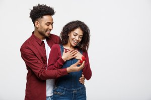 Young handsome african american man surprisingly ask her girlfriend for proposal.