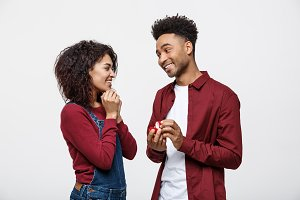 Young handsome african american man surprisingly ask her girlfriend for proposal