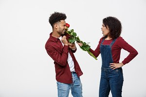 Portrait of a disappointed young woman holding red rose with while standing and angry on her boyfriend isolated over white background