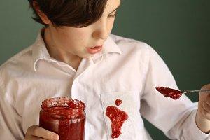 teenager untidy boy drop jam from jar to white shirt make dirty spot