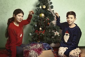 teen girl and boy decorating christmas tree