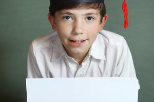 boy in graduation cap with white paper sheet