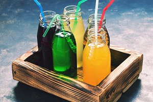 Bright drinks in glass bottles with a straw.