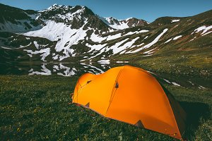 Orange camping tent in mountains