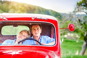 Senior couple in red car
