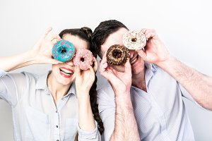 Funny couple with colorful donuts