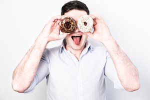 Funny guy holding colorful donuts