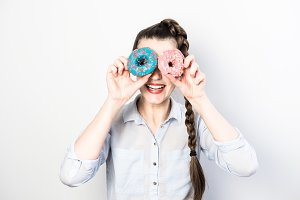 Funny woman holding colorful donuts